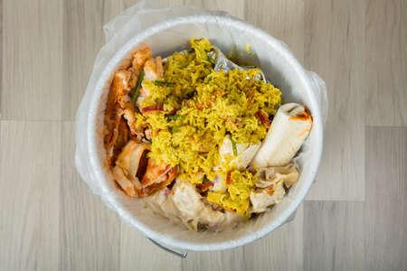 흰색 쓰레기 빈의 근접 남은 음식으로 덮여