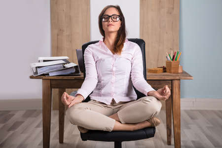 Young Businesswoman Sitting On Chair Meditating In Office Stok Fotoğraf