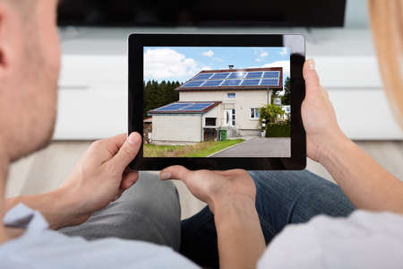 alternative living: Close-up Of Couple Looking At House With Solar Panels On At Digital Tablet Stock Photo
