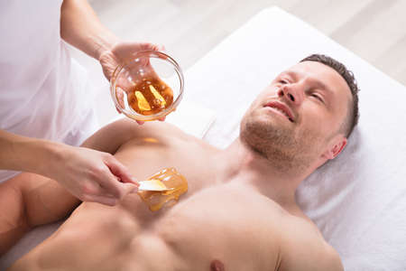 Close-up Of A Therapist Applying Wax On Mans Body Stock Photo
