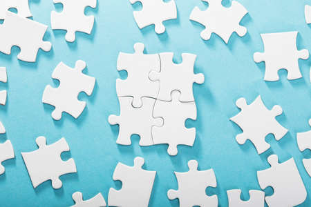 Elevated View Of White Jigsaw Puzzles On Blue Background Stock Photo