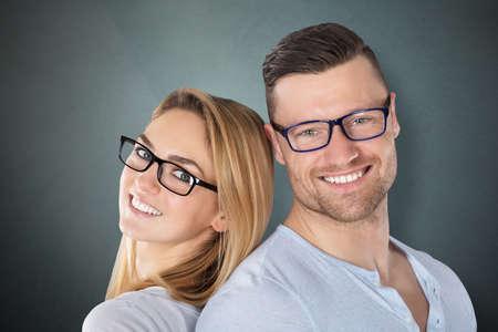灰色の背景にスタイリッシュな眼鏡と幸せな若いカップル