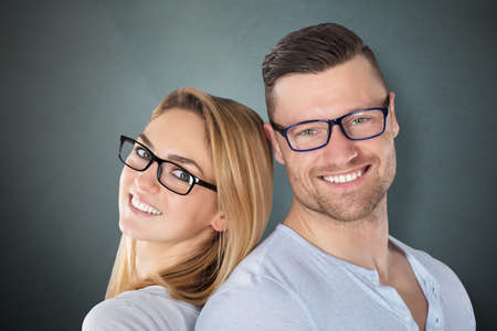 Happy Young Couple With Stylish Eyeglasses Against Grey Background