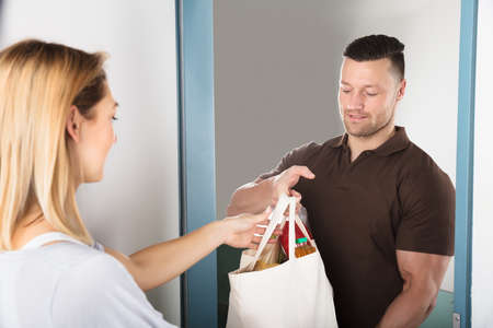 Young Handsome Man Giving Bag Of Grocery To Woman At Home Stock Photo