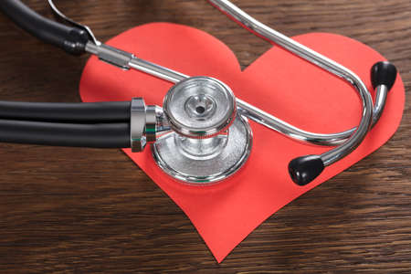 Close-up Of A Red Heart With Stethoscope On Wooden Desk