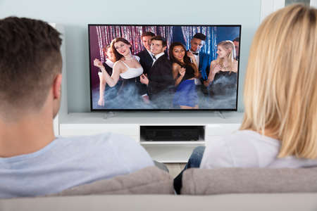 couple on couch: Rear View Of A Couple Watching The Young People Dancing In Television Stock Photo