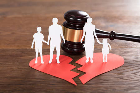 Close-up Of A Family Paper Cut On Broken Heart With A Gavel At Wooden Desk Standard-Bild