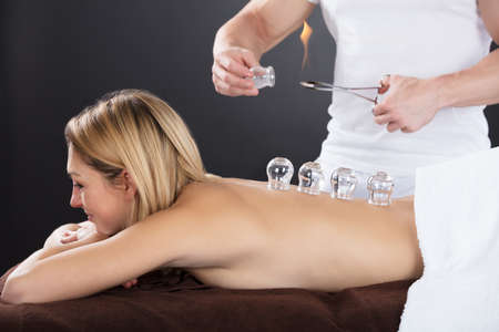 cupping glass cupping: Smiling Young Woman Lying On Front Receiving Cupping Treatment On Back