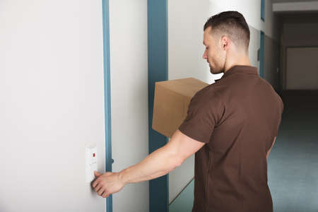 Close-up Of A Delivery Man Holding Cardboard Box Ringing The Door Bell Stock Photo