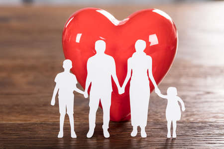 Close-up Of A Family Health Concept With Family Cut-out And Red Heart On Wooden Desk