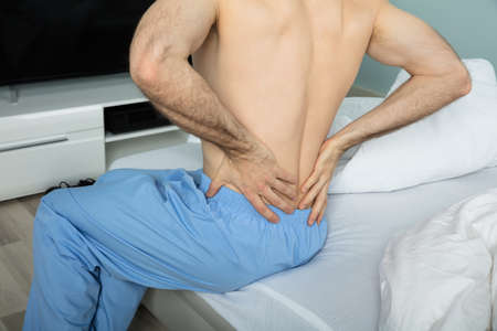 bedsheet: Close-up Of A Man Sitting On Bed Suffering From A Back Pain At Home
