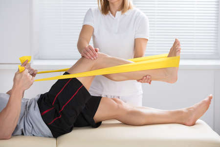 Close-up Of A Female Physiotherapist Giving Treatment With Exercise Band Banco de Imagens