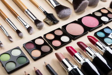 Verschillende soorten make-upborstels en make-upproducten in een rij op beige achtergrond Stockfoto