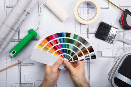 brush painting: Architect Holding Color Guide Swatch On Blueprints With Paint Roller And Paint Brush