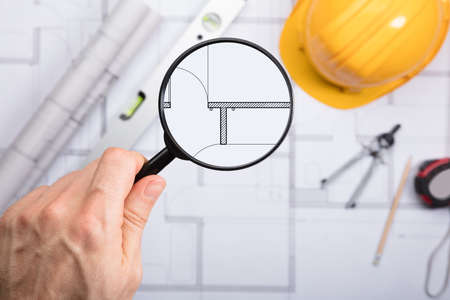 architect drawing: Close-up Of An Engineer Examining The Architectural Blueprint With Magnifying Glass At Workplace Stock Photo