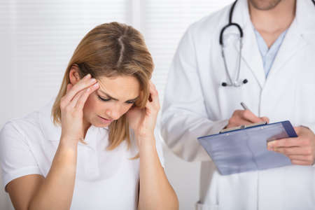 Female Patient With Headache In A Clinic Stock Photo