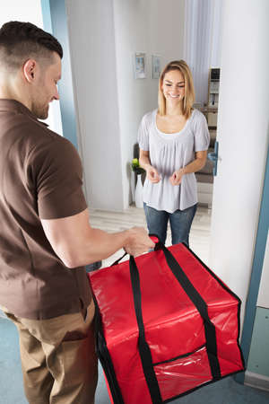 Delivery Man Giving A Large Red Bag To Happy Young Woman Archivio Fotografico