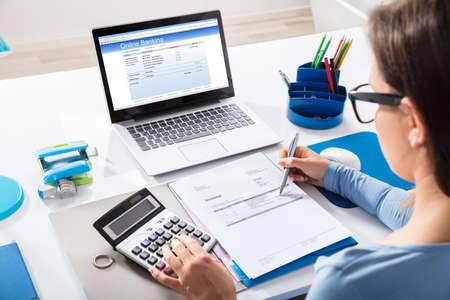 オンライン銀行はノート パソコンの画面上の電卓を使用して請求書を計算する実業家のクローズ アップ