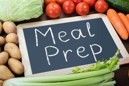 新鮮な有機野菜のスレートに書かれた食事準備言葉の立面図