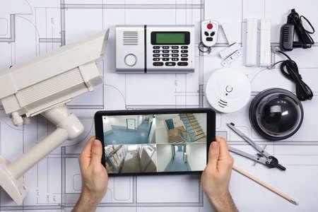 Gros plan d & # 39 ; une personne en regardant des photos sur tablette numérique avec des équipements de sécurité sur le plan Banque d'images - 81079908