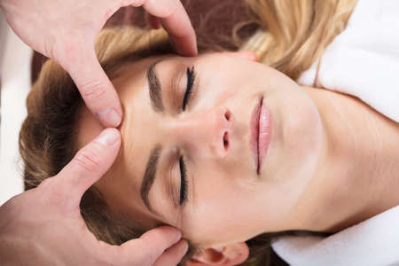 Close-up Of A Therapist Massaging A Beautiful Womans Forehead At Beauty Spa