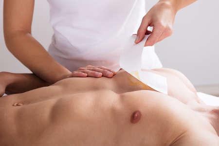Close-up Van Een Vrouw Waxing Man's Bors Met Wax Strip