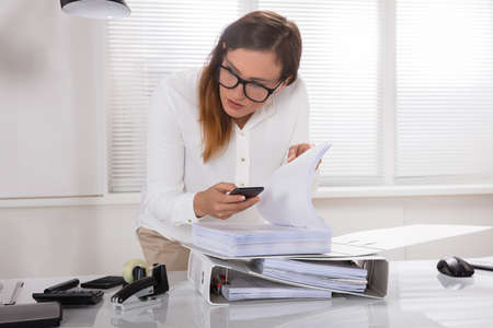 Young Businesswoman Taking Photo's Of Document Secretly Kept On Desk In Office 写真素材