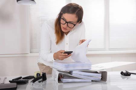 Giovane imprenditrice prendendo foto di documento segretamente tenuto in ufficio in ufficio