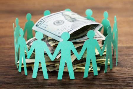 Crowdfunding Concept. Papier snijd de menselijke figuren om de stapel honderd dollarbiljetten Stockfoto - 76436363