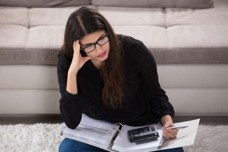 contemplated: Contemplated Young Woman Calculating Bills At Home Stock Photo