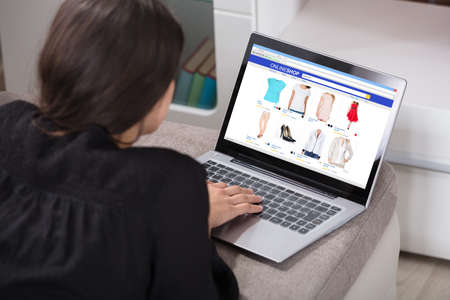 Close-up Of A Woman Lying On Couch Shopping Online Using Laptop photo