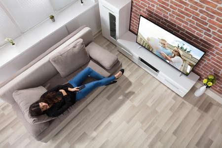 家でテレビを見てソファの上に横たわる女性の立面図