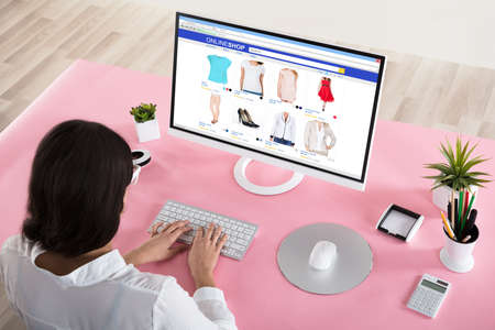Rear View Of A Businesswoman Shopping Online With Pink Desk In Office Stok Fotoğraf