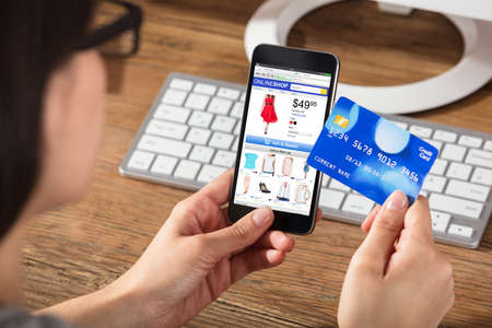 Woman Doing Online Shopping Using Cell Phone And Credit Card photo