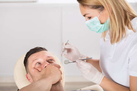 Close-up Of A Young Man Scared Of Dentist In A Clinic