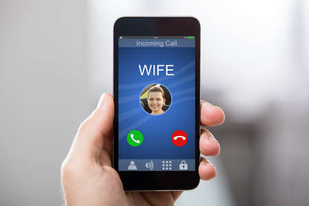 incoming: Close-up Of A Hand Holding Smart Phone With Wifes Incoming Call On Display