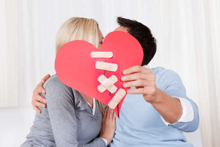 Kissing Couple Holding Paper Red Heart Fixed With Plaster Bandage In Front Of Their Faces photo