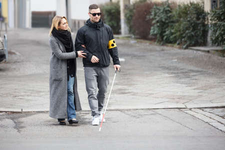 aide a la personne: Young Woman Assisting Blind Man With White Stick On Street