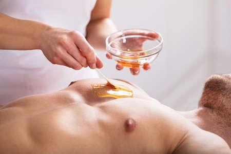 Close-up de um terapeuta que aplica cera no corpo do homem