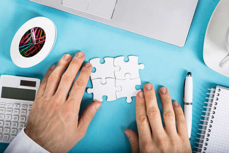 Elevated View Of A Businessperson Joining Puzzle On Office Desk At Work Place Stock Photo