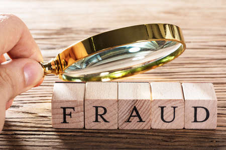 A Person Examining Fraud Blocks Through Magnifying Glass On Wooden Table Stock Photo