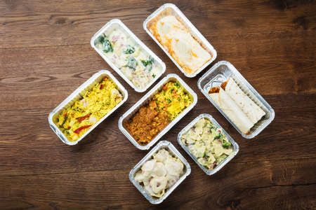 Different Type Of Ready Tasty Meals In Foil Containers On The Table Stock Photo - 77052517