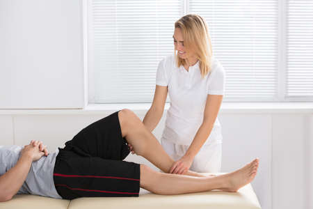 Smiling Female Physiotherapist Giving Knee Therapy To A Man In Clinic