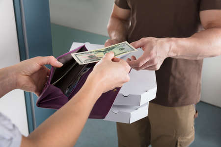 cash money: Close-up Of Woman Giving Us Dollar Note To The Pizza Deliver Man