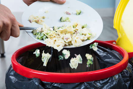 Close-up Of A Person Throwing The Leftover Pasta Into The Trash Bin