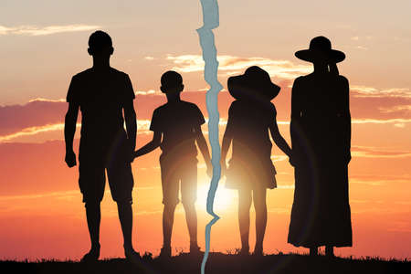 Silhouette Photo Of A Family With Crack Against The Dramatic Sky At Sunset photo
