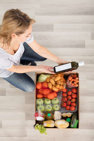 boite carton: Elevated View Of Young Woman Looking At Grocery Box