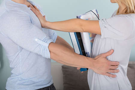 Close-up Of A Woman Holding Folders Pushing A Man Back Stock Photo