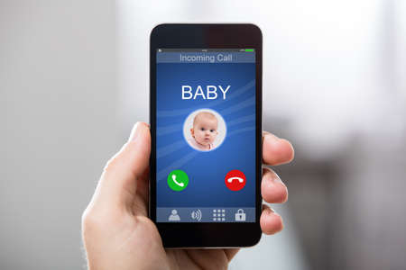 Hand Holding Smart Phone With Babys Incoming Call On Display