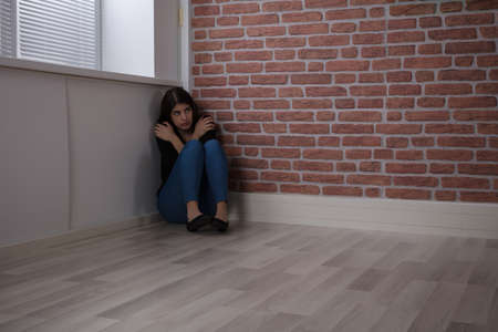 Young Woman Sitting On The Corner Of A Room With Fear At Home